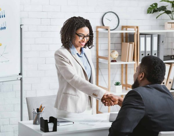 Black hiring manager shaking hands with successful vacancy candidate after work interview at office, copy space