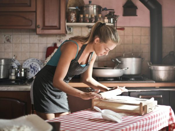 young-woman-rolling-dough-for-baking-in-kitchen